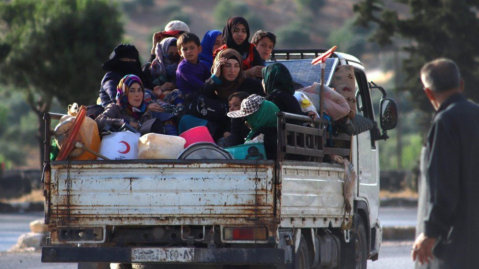 Displaced Syrians sit in the back of a lorry as they flee along the M4 highway, in Ariha, Idlib province (8 June 2020)