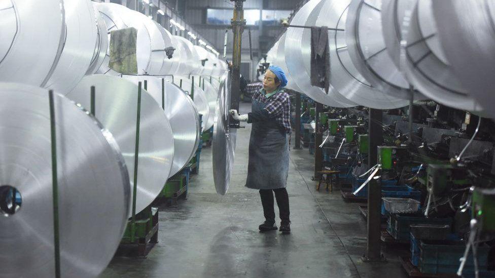 An employee handles aluminium material in Hangzhou, Zhejiang Province of China.