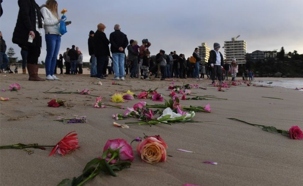Relatives and friends hold a dawn vigil at Sydney's Freshwater Beach