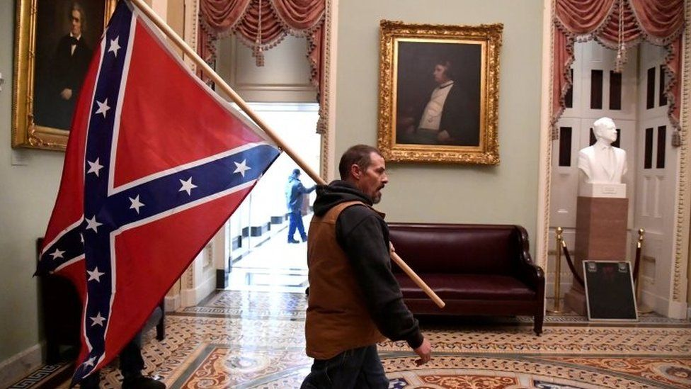 A supporter of President Donald Trump carries a Confederate battle flag on the second floor of the US Capitol