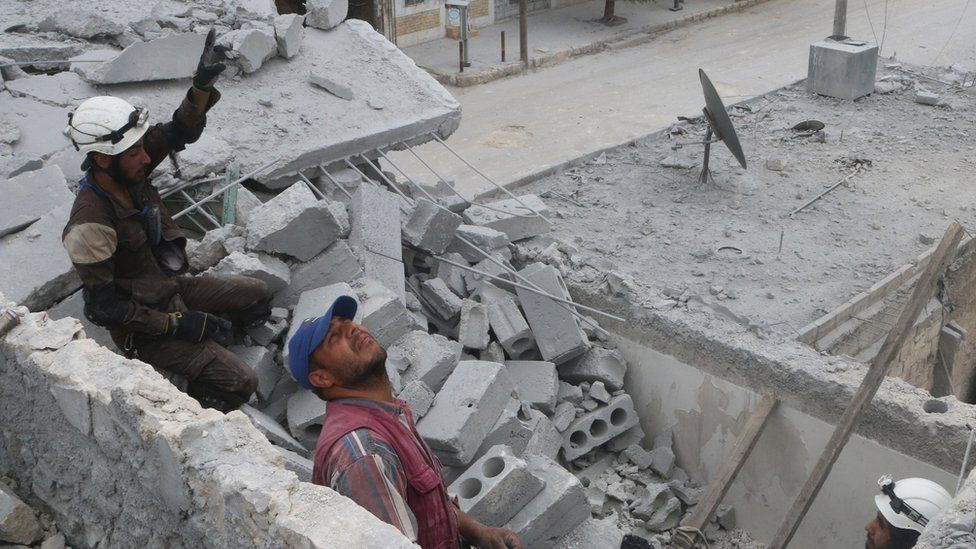 Rescue workers work inside a damaged building after an air strike in the rebel-held Baedeen district of Aleppo, Syria (3 May 2016)