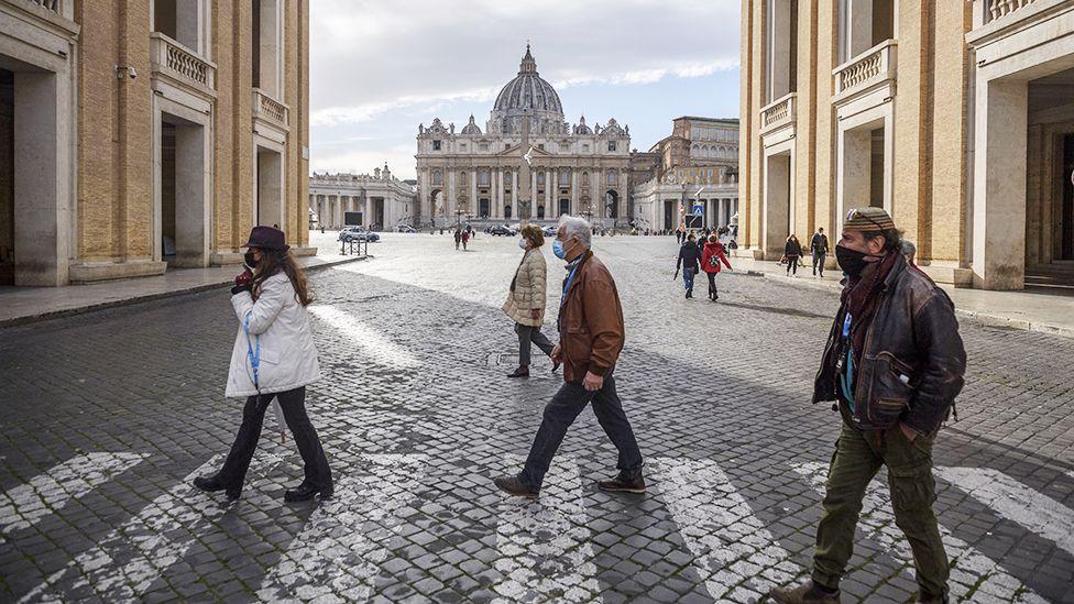 Люди в масках перед собором Святого Петра в Риме