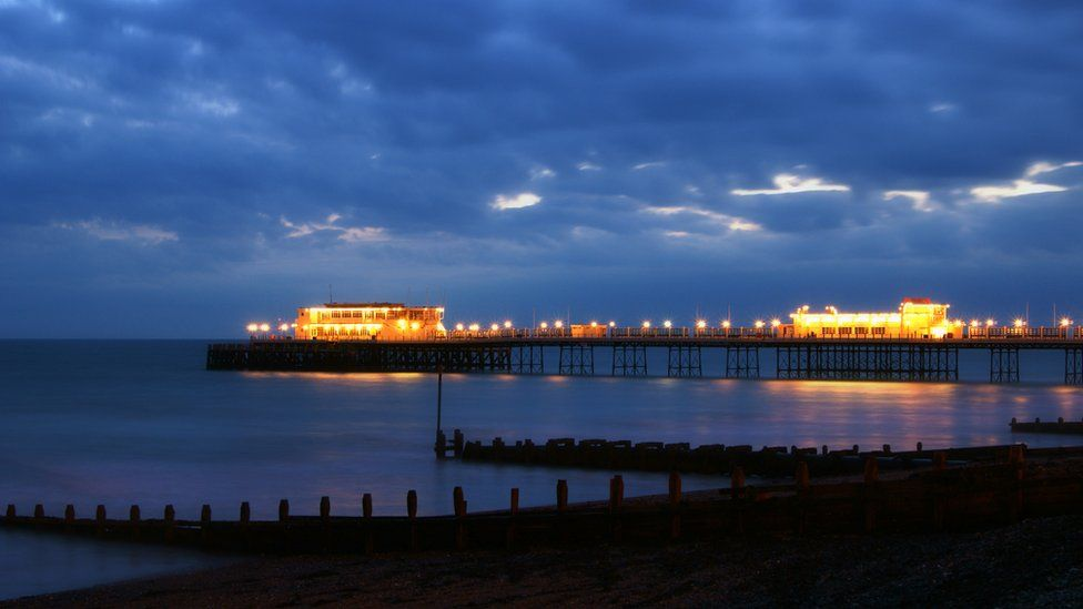 The illuminated pier glows against a cloudy evening sky