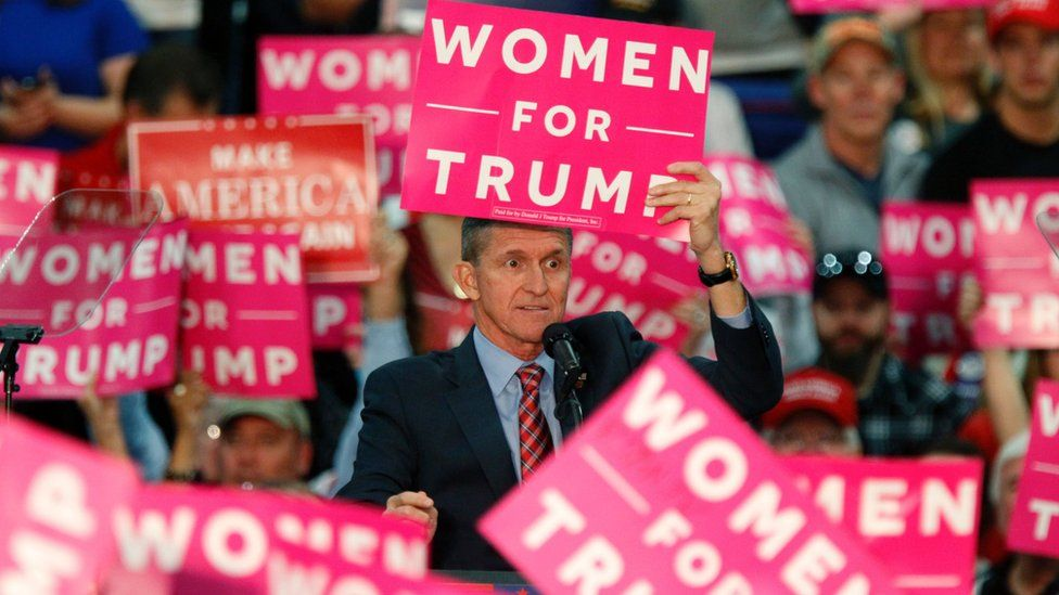 General Flynn hold a pink Women for Trump sign against his head during an election rally
