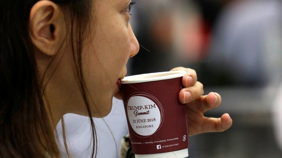 A woman drinks coffee in a cup bearing the sign of the summit between the US and North Korea in Singapore, 10 June