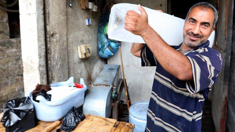 Iraqi man cuts a block of ice to sell it in Baghdad, Iraq, 6 July 2017