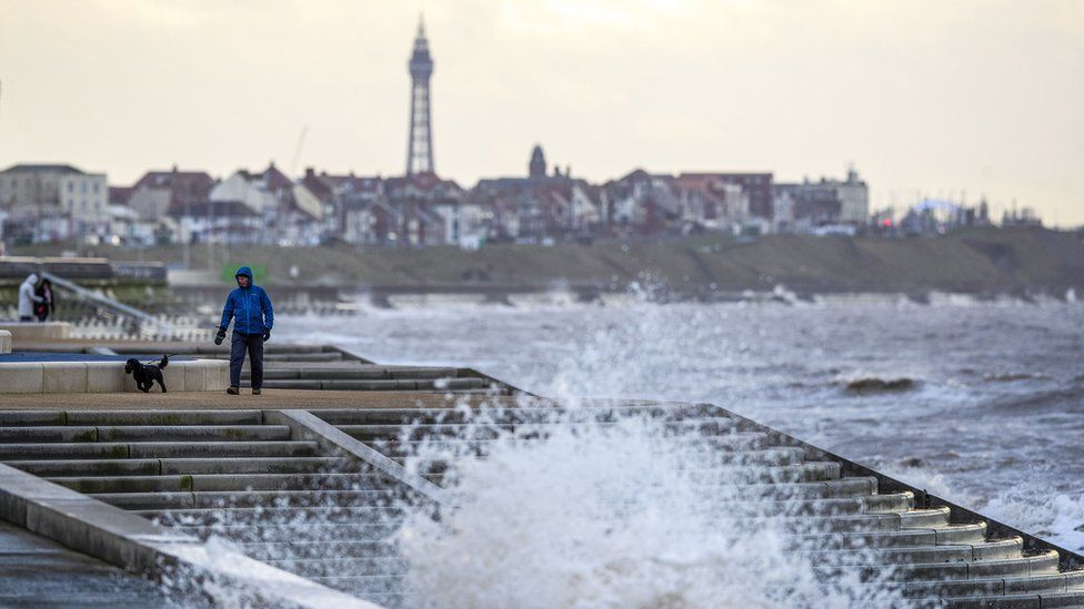 A man walks a dog along the promenade near Blackpool as gusts of up to 80mph could hit parts of the UK as Storm Brendan sweeps in.