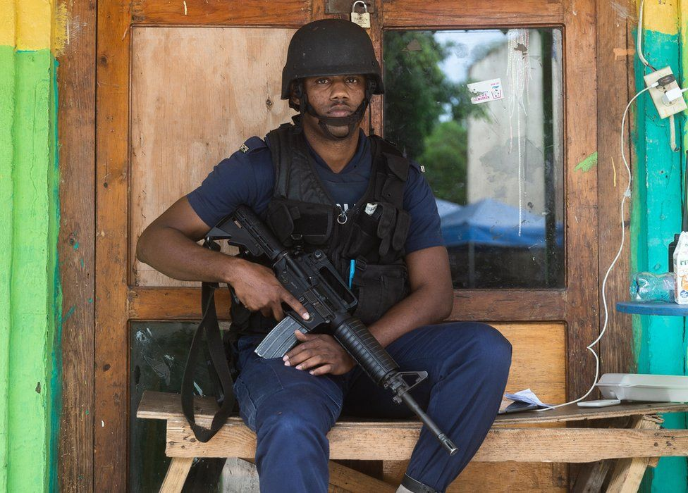 A police officer cradles his weapon while on patrol in Denham Town