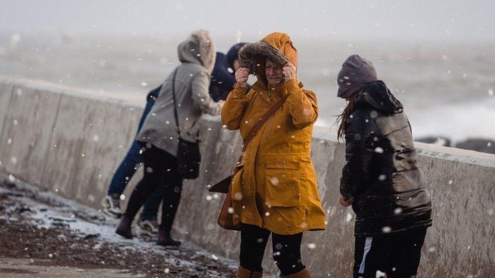 People walk through flying sea foam spray on Sunday in Porthcawl, Wales