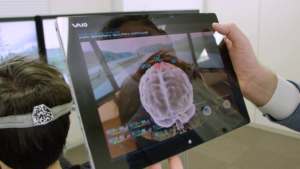 Scientist hold tablet showing image of brain behind test subject's head
