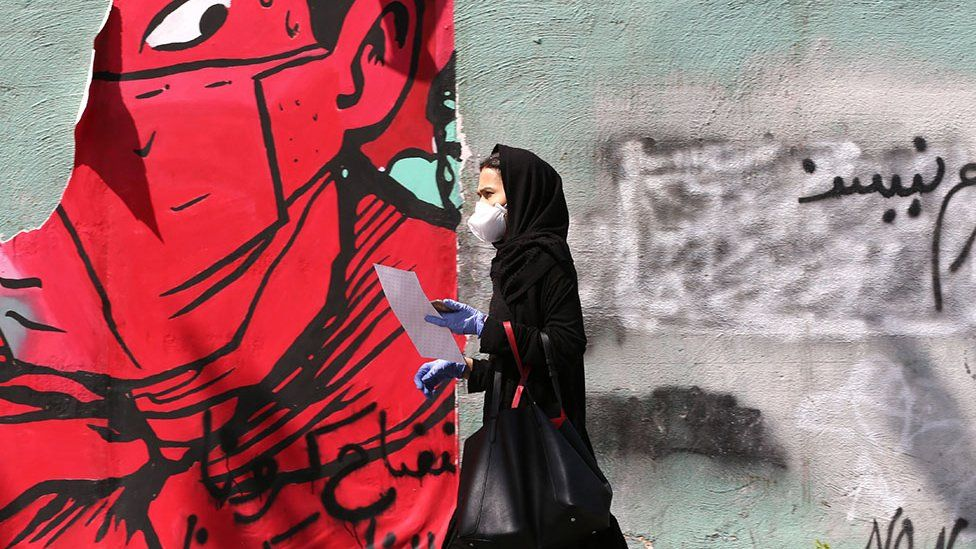 Woman walks past graffiti in Tehran