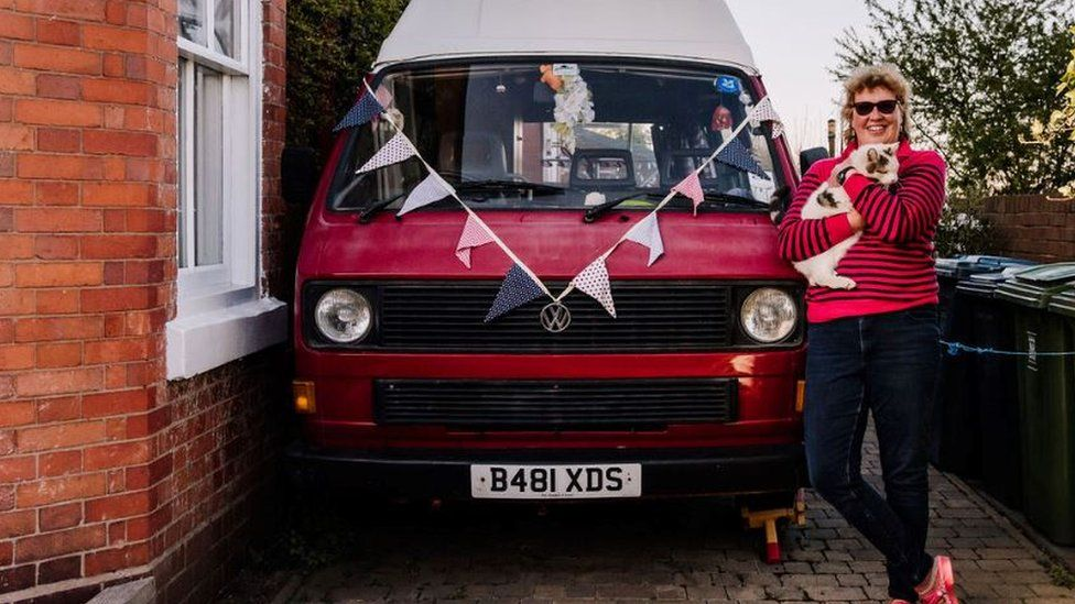 A woman poses with her dog next to her campervan