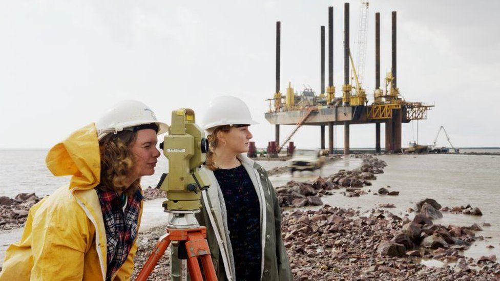 Women do measurements at bridge site