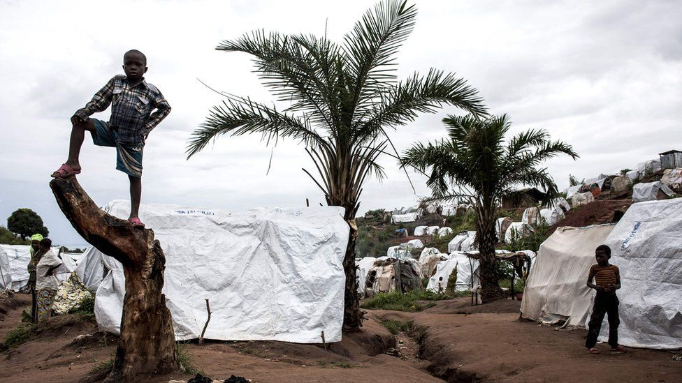 A young Congolese boy stood on a tree stump at a camp for Internally Displaced Persons in Kalemie, Democratic Republic of the Congo. Behind him are two large palm trees and several makeshift camps.