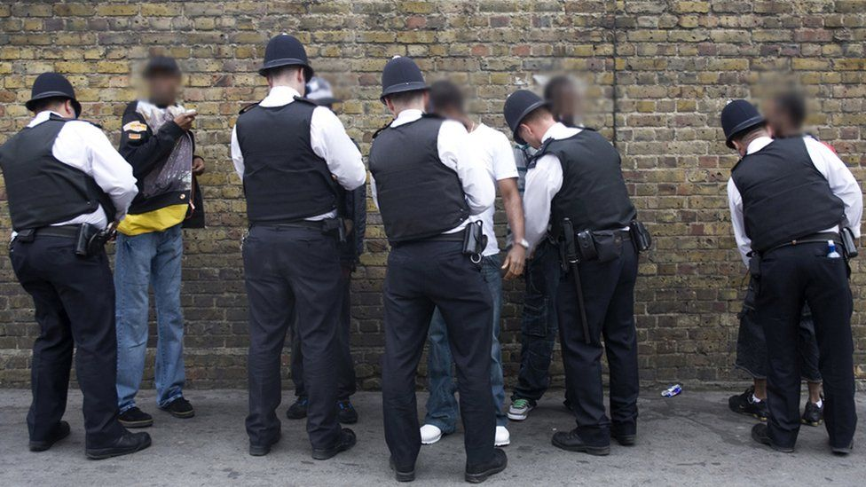 Police search a group of people