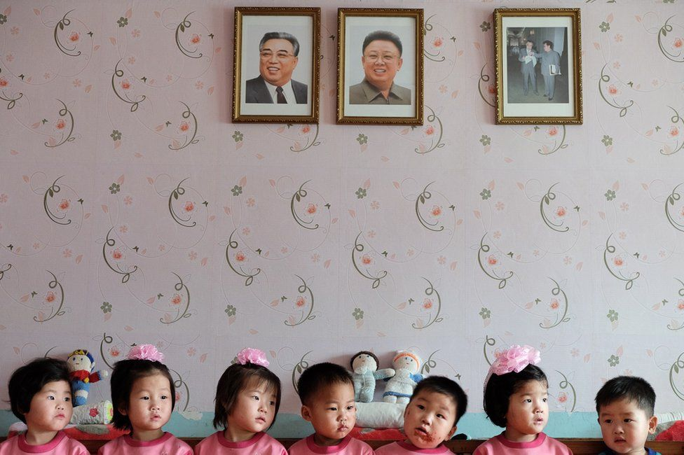 Young children in an orphanage sitting beneath portraits of Kim Il-sung and Kim Jong-il