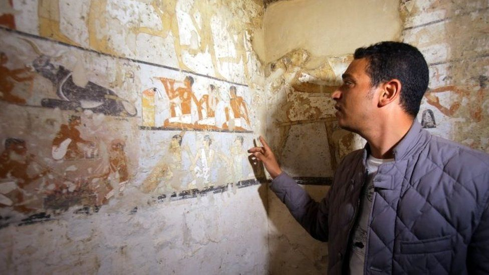 An Egyptian archaeologist points to wall paintings inside the tomb of an Old Kingdom priestess on the Giza plateau on the southern outskirts of Cairo, Egypt, 3 February 2018.