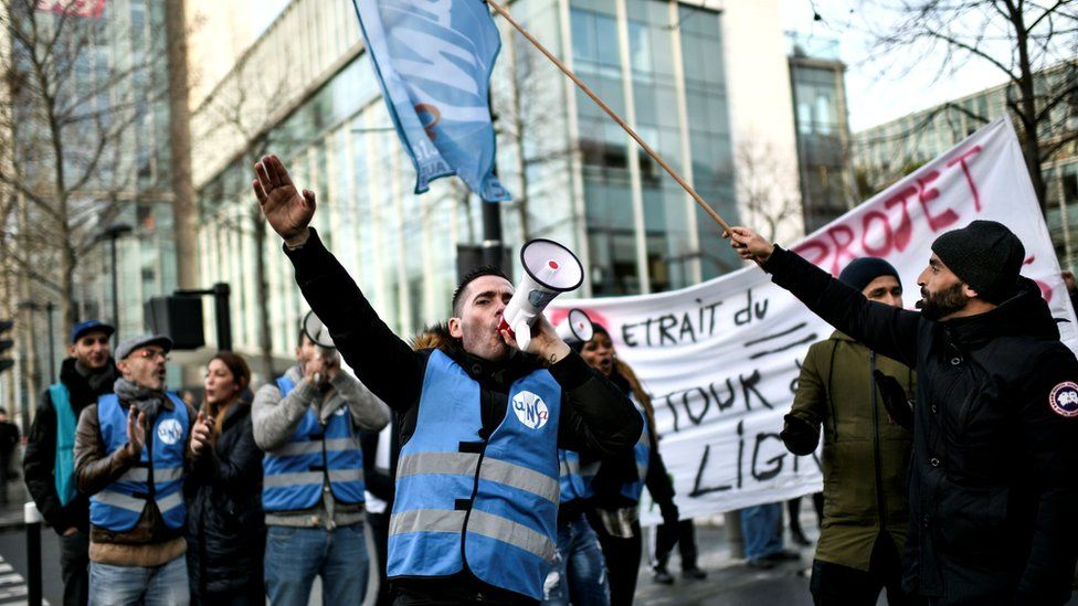 Members of a transport union gather outside French train operator SNCF headquarters in Saint-Denis, near Paris, 24 December 2019