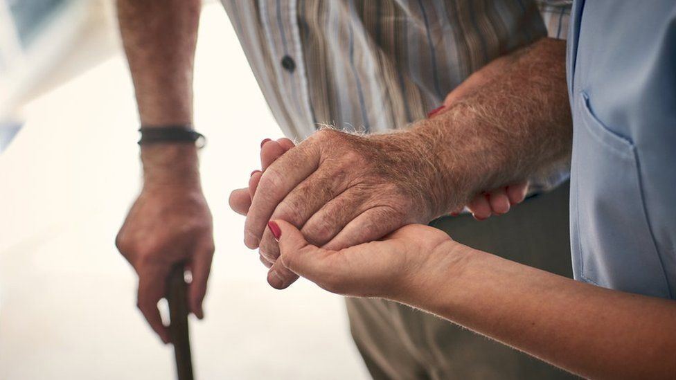 A staff member holds the arm of an elderly man