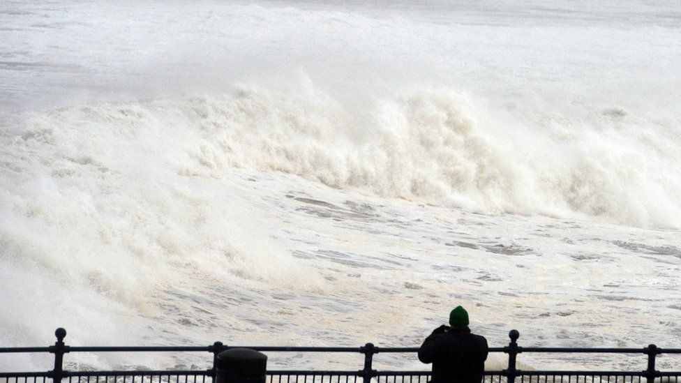A man watches rough waves come in at Portstewart beach