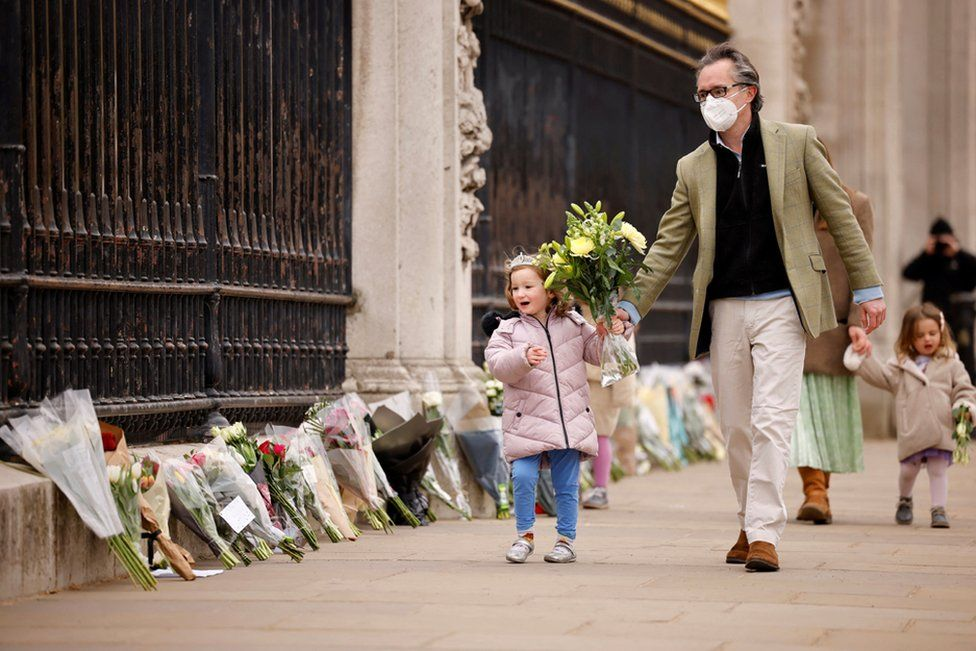 A child carries a floral tribute to Britain's Prince Philip, Duke of Edinburgh outside Buckingham Palace, central London on 10 April 2021