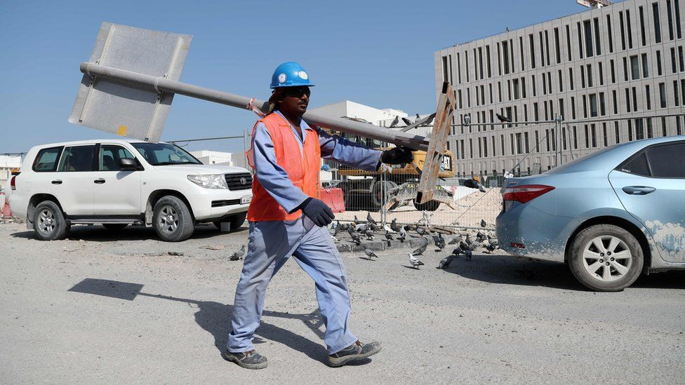 A migrant worker carrying a pole at a construction site in the Qatari capital Doha