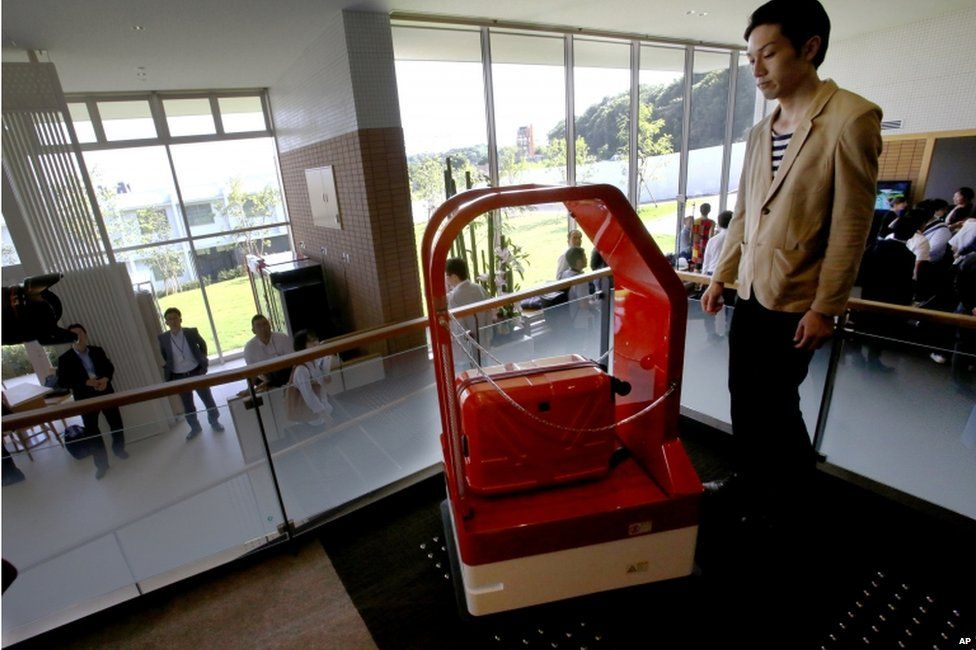 A porter robot, left, escorts a hotel employee while carrying his suitcase during a demonstration for the media at the new hotel, aptly called Henn na Hotel or Weird Hotel, in Sasebo, southwestern Japan, Wednesday, 15 July 2015