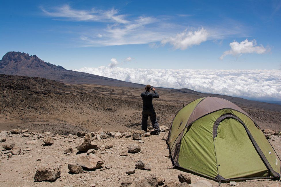 Person taking a photograph outside a tent at high altitude