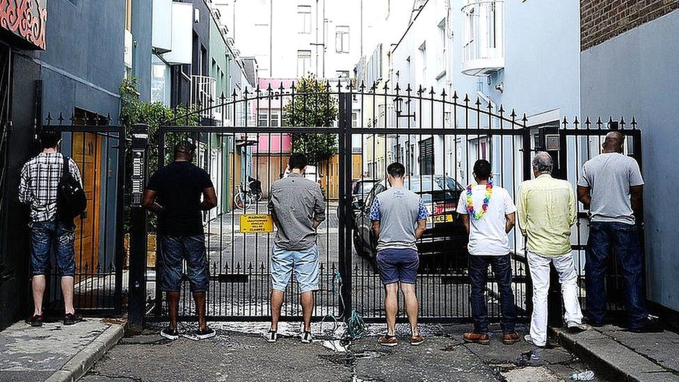 Men urinate on the gates of a mews street during the Notting Hill Carnival 2013