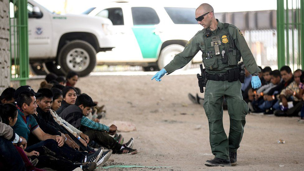 A border official pointing at migrants caught after crossing the US border