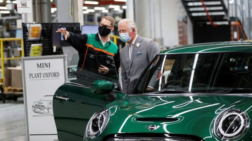 The Prince of Wales speaks to an employee during a visit to the MINI plant in Oxford