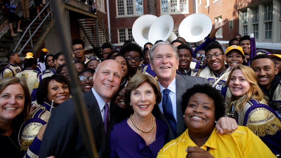 """Former President George W. Bush poses for a """"selfie"""" photo with former first lady Laura Bush, marching band director Asia Muhaimin, right, and New Orleans Mayor Mitch Landrieu, left, at Warren Easton Charter High School in New Orleans on 28 August"""