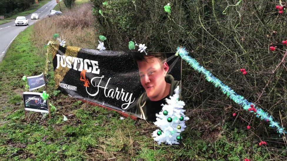 A Christmas tree and decorations surround a banner for Harry Dunn outside RAF Croughton