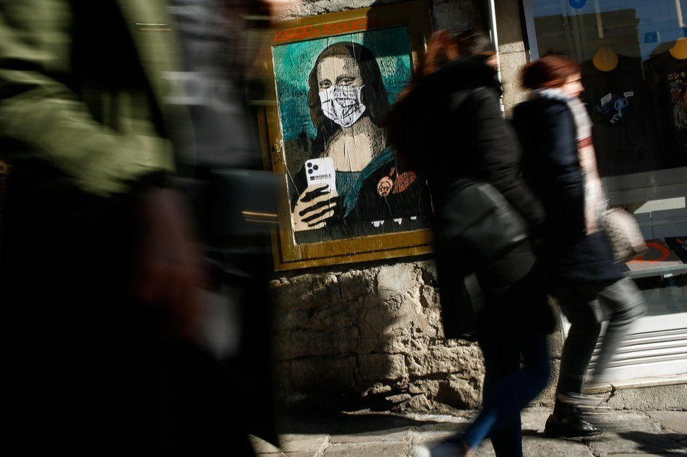 """People walk by a poster by Italian urban artist Salvatore Benintende aka """"TVBOY"""" depicting Leonardo da Vinci's Mona Lisa wearing a protective facemask and holding a mobile phone, 18 February 2020."""