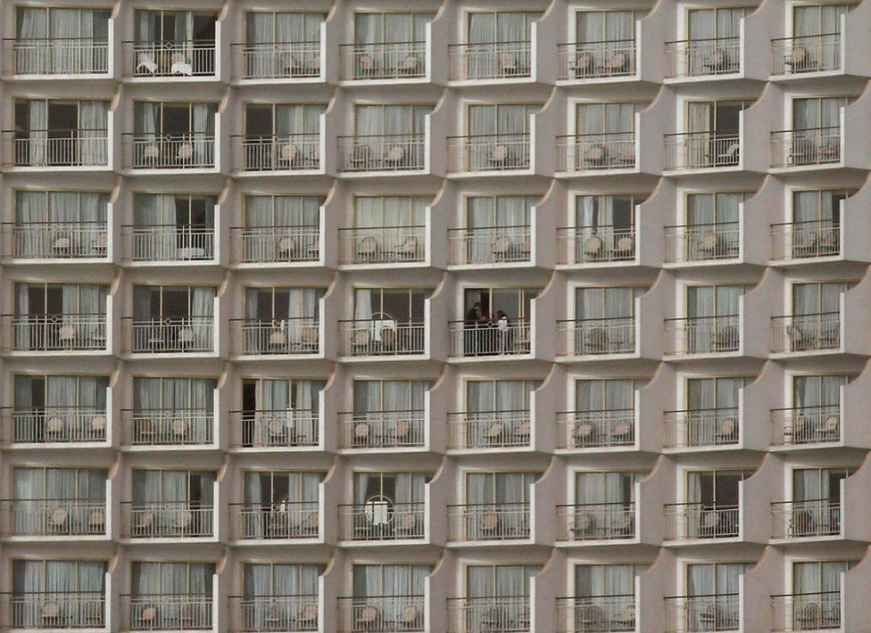 People stand on a hotel balcony. Dozens of other balconies are also visible, but they are empty in Cairo, Egypt - Tuesday 16 February 2021
