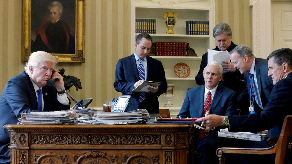 President Trump (left) speaks to Vladimir Putin on the White House phone