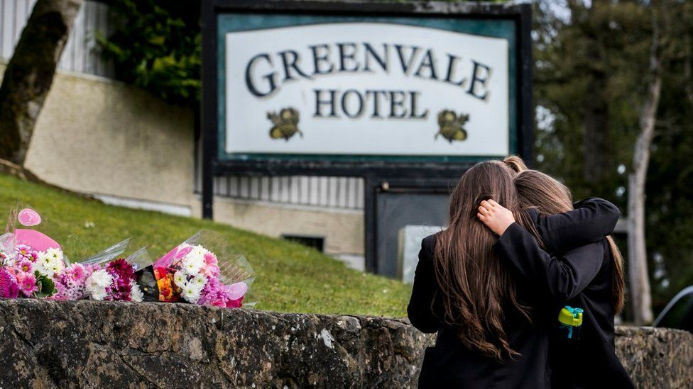 Schoolgirls lay flowers at the Greenvale Hotel