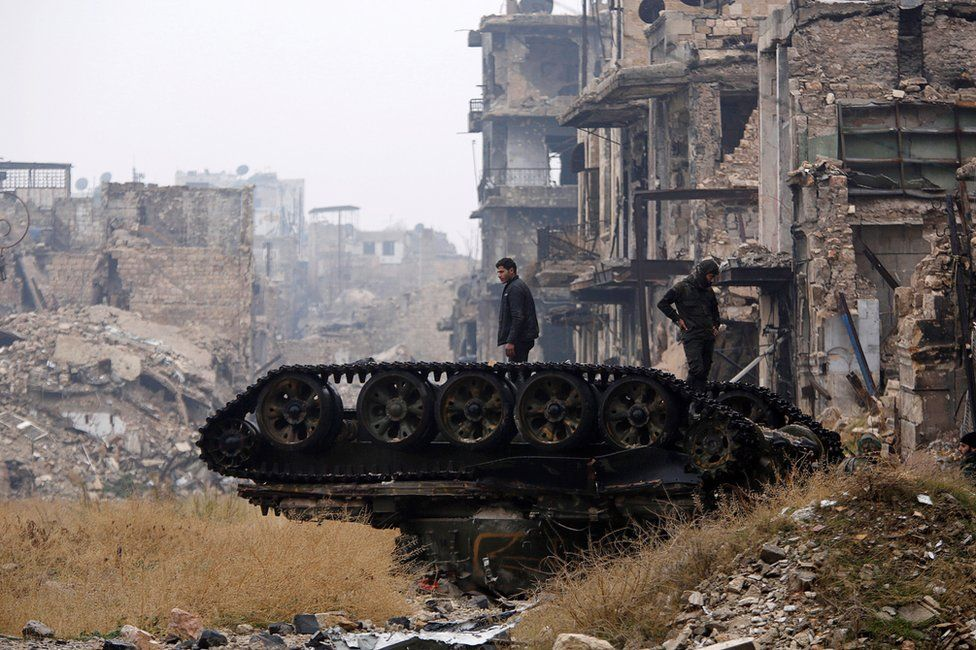 Forces loyal to Syria's President Bashar al-Assad stand atop a damaged tank near Umayyad mosque, in Aleppo, 13 December