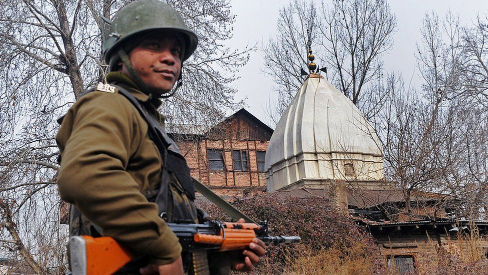 An Indian paramilitary soldier stands guard outside Sheetleshwar Bhairav, one of the valley's oldest and largest Hindu temples, in Srinagar on January 20, 2010 as Kashmiri Pandits perform rituals inside the tempt to mark its re-opening after 21 years.