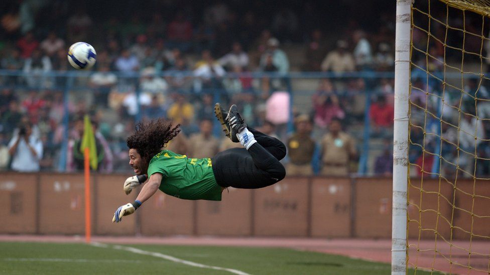 Former Colombian goalkeeper Rene Higuita kicks the ball to save a goal during an exhibition match between the Brazilian Masters and Indian All Stars in Kolkata on December 8, 2012