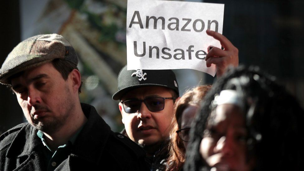 Amazon workers with an Amazon Unsafe sign