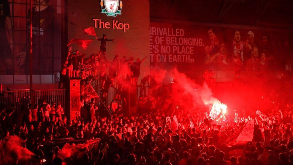 Crowd of Liverpool fans in front of The Kop celebrating Premier League title win