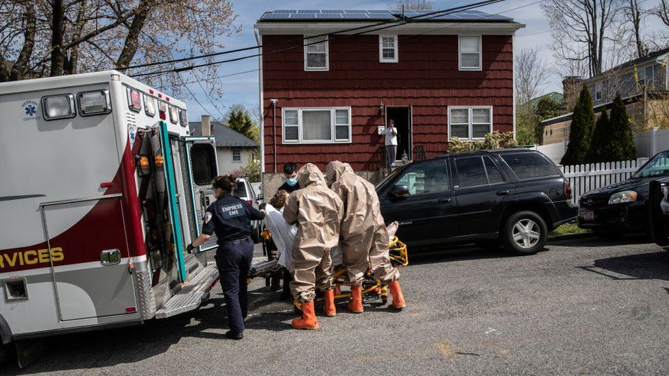 Yonkers Fire Department EMTs, clothed in full personal protective equipment (PPE), assist Empress EMS EMTs to transport a patient with COVID-19 symptoms to a hospital on 14 April, 2020