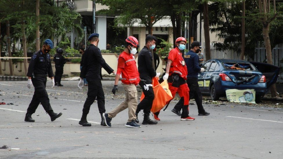 Red Cross personnel carry a body bag following an explosion outside a Catholic church in Makassar