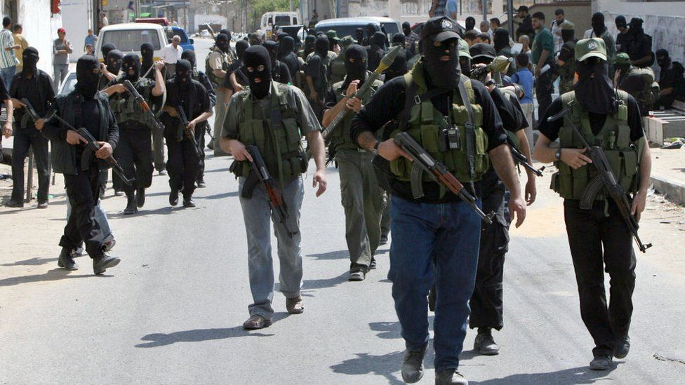 Hamas militants march towards the Palestinian Preventative Security headquarters during clashes in Gaza City on 14 June 2007
