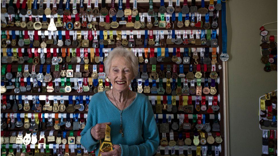 Deirdre Larkin stands in front of a wall with her medals on it.