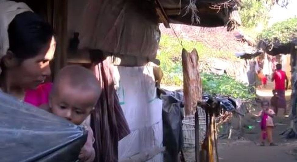 A woman holding a baby looks at another child in her village