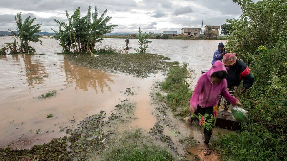 """Workers take a makeshift boat to cross flooded vegetable gardens in Madagascar""""s capital Antananarivo, on Thursday, March 9, 2017"""