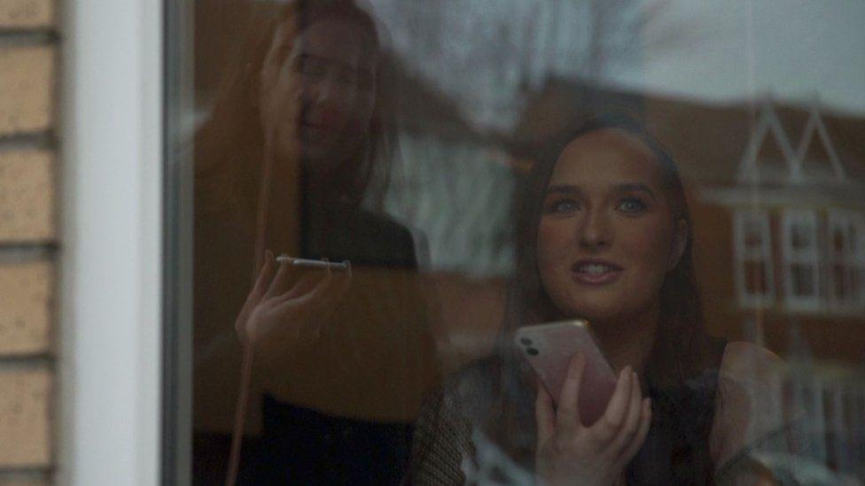 Ella Ounsworth speaking to Alex through a window.