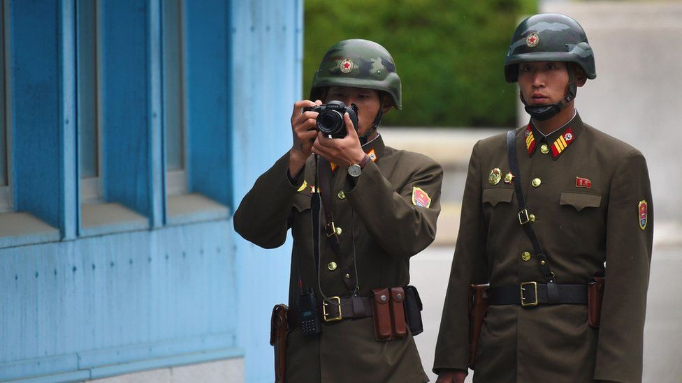 A North Korean soldier takes a photo as two soldiers look at the South side while US Vice President Mike Pence visits the truce village of Panmunjom in the Demilitarized Zone (DMZ) on the border between North and South Korea on 17 April 2017